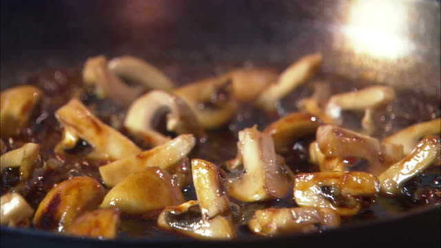 Extreme close up zoom out zoom in mushrooms being sauteed in skillet / Auckland, New Zealand