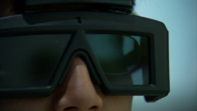 Extreme Close Up_hand-held - Video game images reflect off the lenses of a pair of virtual reality glasses as a gamer plays.