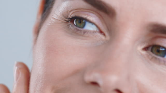 Extreme close-up of radiant 40yrs+ woman touching face