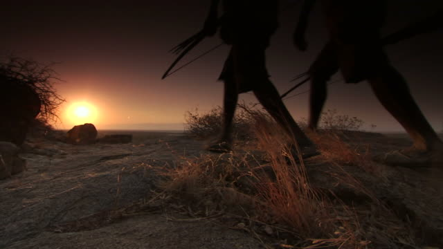 Extreme Long Shot crane - Two tribesmen carry bows and arrows as they walk through the desert as the sun sets. / Hadza, United Republic of Tanzania