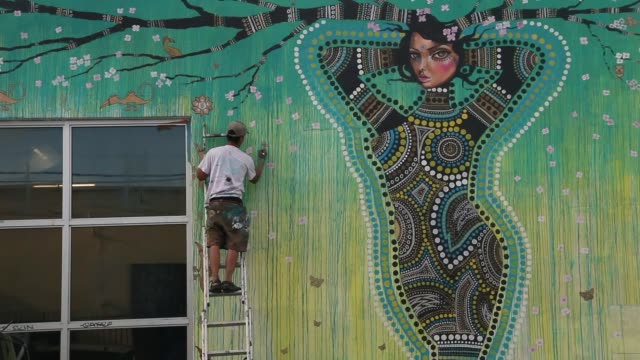 Extreme Long Shot Luis Valle works on a painting on the side of a building in the Wynwood section of Miami on August 12 2013 Murals by renowned...