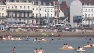 Extreme long shot People enjoy the warm weather on the beach at Weymouth