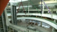 Extreme Long Shot tilt-down - Construction workers use a walkway in the atrium of a Hongqiao Airport terminal./Shanghai, China