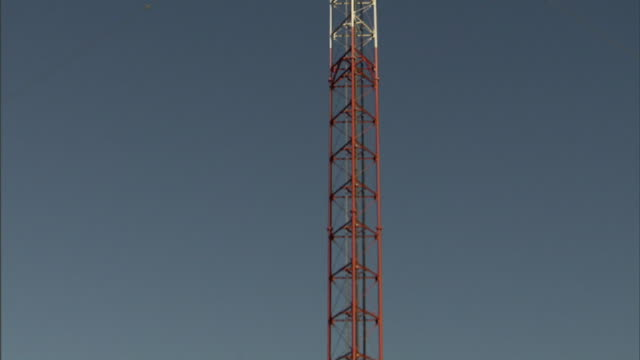 Extreme Long Shot tilt-up zoom-in - A radio tower contrasts against a blue sky. / North Carolina, USA