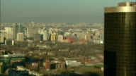 Extreme Long Shot zoom-in - The city of Beijing sprawls beyond a contemporary downtown office building./Beijing, China