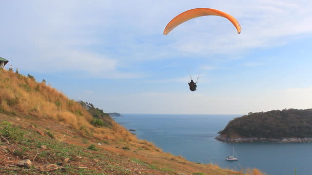 Extreme Sports - Paragliding over the Sea clear blue sky