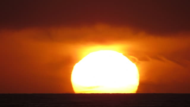 Extremely Large Sun Sets Into Stormy Orange Cloudy Ocean
