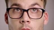 Eyes of a young Caucasian man wearing eyeglasses looking around