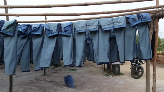 Fabric dyeing machines operate in a jeans factory at an apparel park in the Workers hang denim jeans outside the Krishna Jeans Washers factory at an...