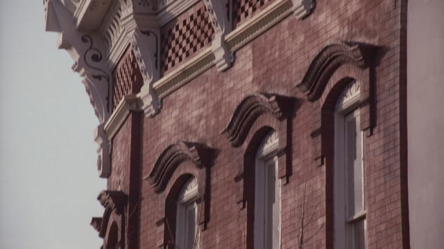 TU Facade of an ornate, brick building with corbels and intricate stone designs / Washington, District of Columbia, United States