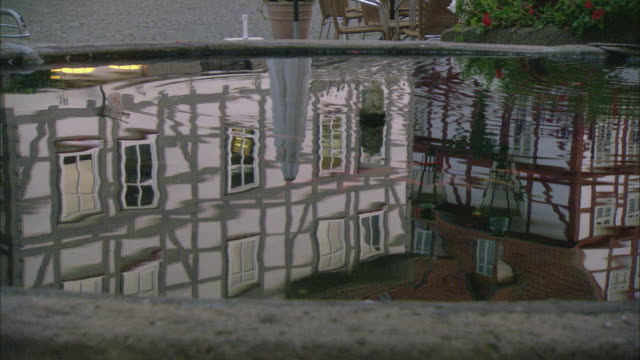 CU Facades of half-timbered buildings reflected in water of fountain / Kassel, Germany