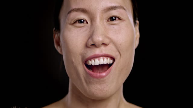 Face of an Asian woman laughing