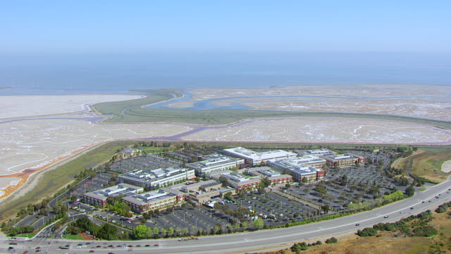 WS AERIAL POV Facebook headquarters campus area with desert and sea, car moving on street seen in foreground / Menlo Park, California, United States