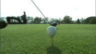 Young adult male golfer hand pushing tee in ground placing golf ball on top while leaning on driver positioning driver behind ball teeing off golfer...