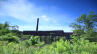 Factory building w/ smoke stack wispy white clouds in blue sky body of water canal or river tall green grass/weeds FG