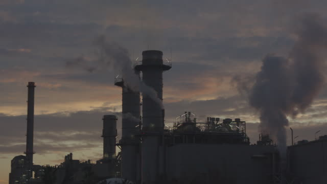 Factory expels steam at sunset with the lights turned on