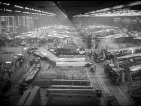 Factory floor w/ B47 Stratojets in lines supplies parts FG BEHIND Three men in suits watching wing attaching HA WS Crews working on sweptback wings...