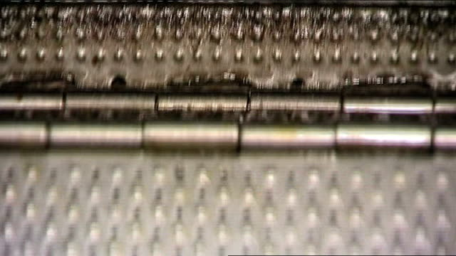Metal components ENGLAND West Midlands INT Closeup of steel components on factory production line conveyor belt mechanism dropping completed nuts and...