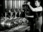 Factory smoke stacks INT MS English man operating drill press CU Worker w/ machine CU Woman operating machine MS Man w/ welding machine sparks...