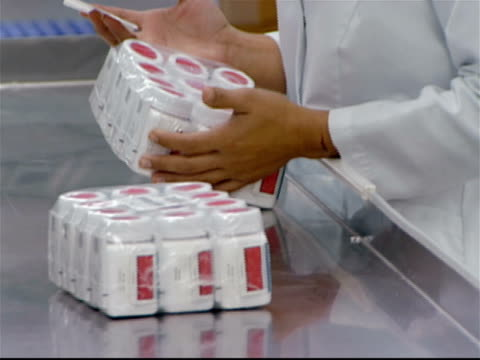 Factory worker labeling packaged pill bottles off assembly line / stacking on palette / Puerto Rico