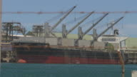 Fading from a barbed wire fence to a cargo ship 'Nord Ocean' sitting in 'Karara Mining's' dock bulk loading facility