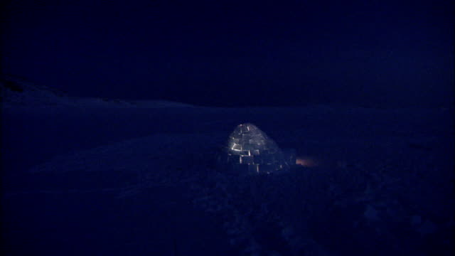 A faint glow shines from an igloo at night. Available in HD.