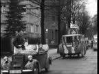 Fake tank followed by a Radio Propaganda car and many other cars in a Berlin convoy Winter