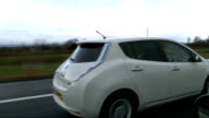 Falling popularity of electric cars ENGLAND from moving car as drives from slip road onto motorway Speedometer on dashboard of electric car View from...