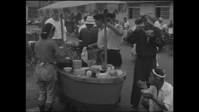 Families enjoy food in an outdoor Tokyo market.