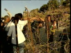 Families wave to each other across barbed wire fence at Israel/Lebanon border May 2000