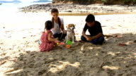 Family and dog play with sand