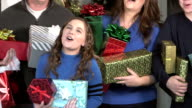 Family at front door with Christmas gifts, singing