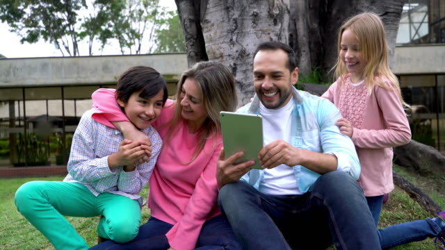 Family at the park outdoors looking at photos on a tablet