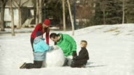 Family buiiding a snowman