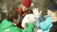 Family builds a snowman togther