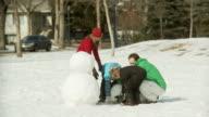 Family builds a snowman