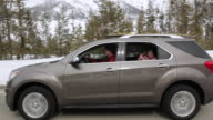 MS POV Family car driving at snowy day and little girl waving hand at back window / Sun Valley, Idaho, United States