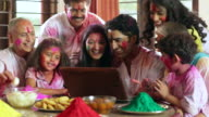 Family celebrating holi festival on the laptop