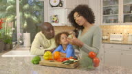family  chopping vegetables in kitchen