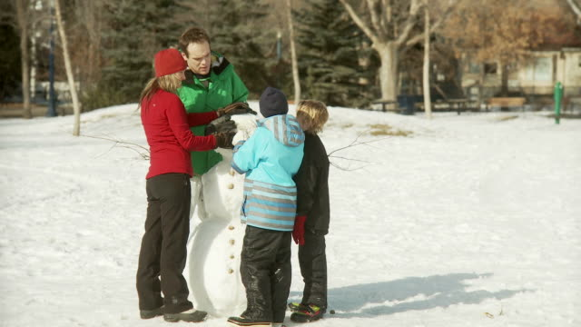 Family conrstucts a snowman