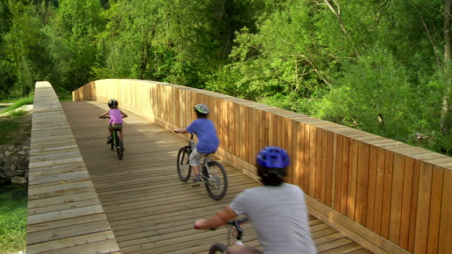 Family Cycling Across The Bridge