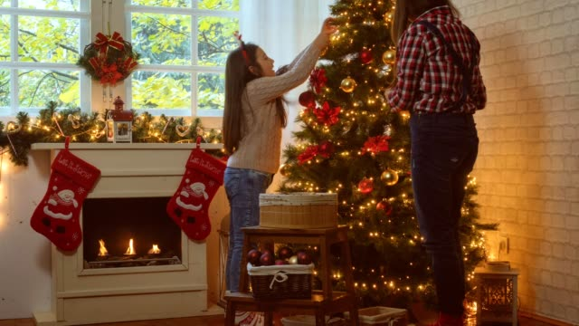 Family decorate the Christmas tree at home