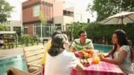 Family eating breakfast at poolside in a farm house