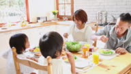 MS  Family eating breakfast in kitchen / Fujikawaguchiko, Yamanashi, Japan