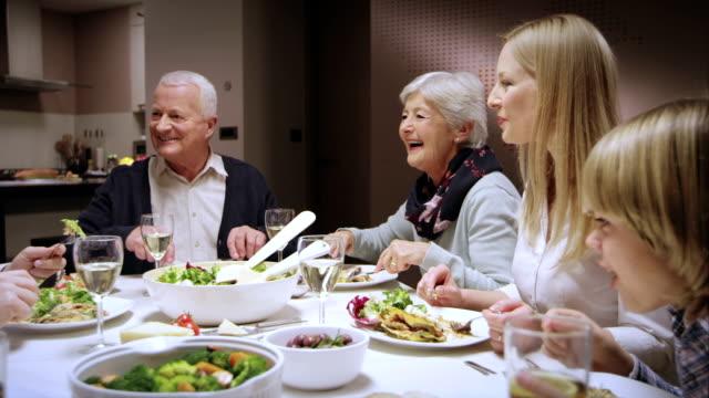 Famiglia godendo la cena al tavolo mangiare e chiacchierare