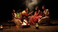 Family enjoying music at campfire