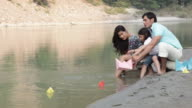Family floating paper boat on the water