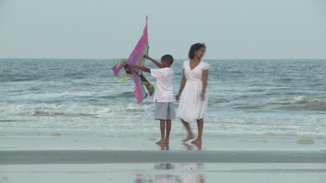 WS TS PAN TD ZI ZO Family flying kite on beach / Jacksonville, Florida, USA