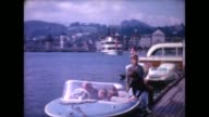 1966 family getting in small boat on Lake Lucerne and pulling away