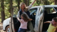 MS family getting out of car in forest and hugging